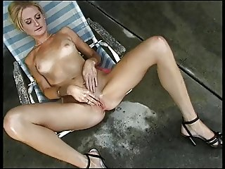 Slim blonde in lounge chair plays with her clit then slides dildo into her cunt