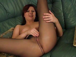 Redhead Temptress Shows Pink Pussy Through Black Pantyhose