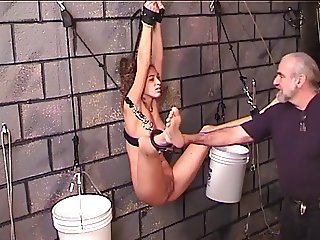Young Nicole hangs bound to the dungeon wall and prodded with metal object