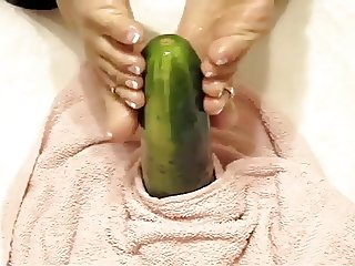 Oiled soles stroking a cucumber