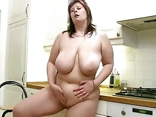 Plump babe with big boobs masturbates in the kitchen.