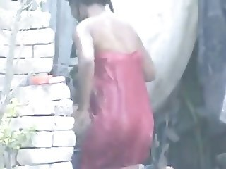 neighbour girl bathing outside in village
