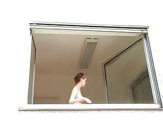 Gorgeous redhead cleaning window